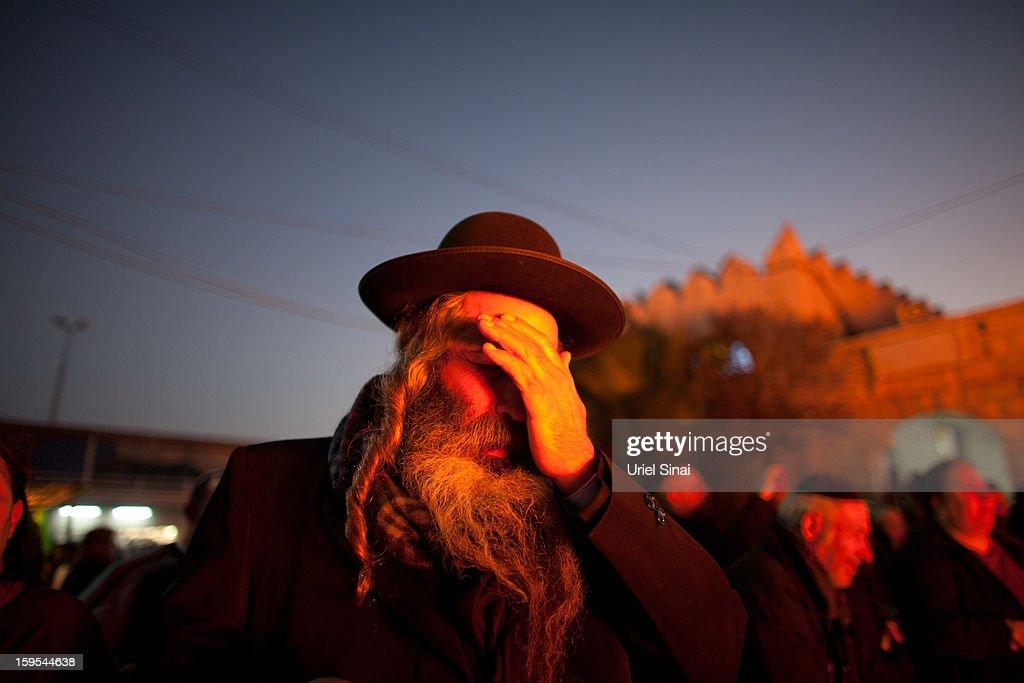 A Jewish man prays alongside a burning pyre of votive candles at the grave of Rabbi Yisrael Abuhatzera known as the sage Baba Sali on January 15 2013...
