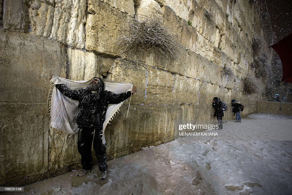A Jewish man prays at the Western Wall as snow falls in the old city of Jerusalem on January 10, 2013. Jerusalem was transformed into a winter wonderland after heavy overnight snowfall turned the Holy City and much of the region white, bringing hordes of excited children onto the streets.