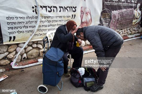 A Jewish man receives a blessing from an older man at the tomb of Rabbi Israel Abuhaeira known as the Baba Sali during the annual pilgrimage to his...