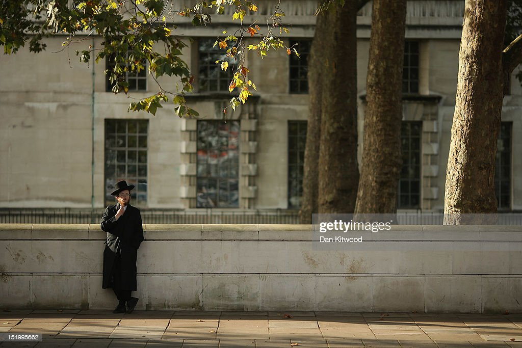 A Jewish man relaxes against a wall on the Embankment on October 30, 2012 in London, England.