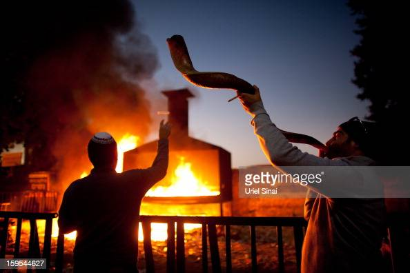 A Jewish man throws votive candles into a burning pyre as another blows a shofar at the grave of Rabbi Yisrael Abuhatzera known as the sage Baba Sali...