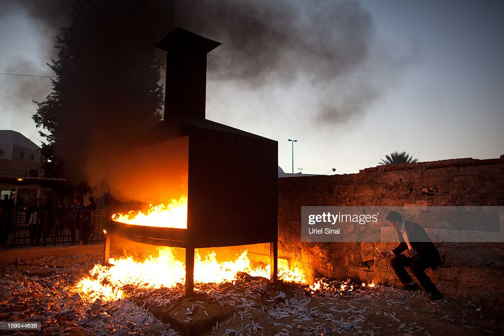 A Jewish man throws votive candles into a burning pyre at the grave of Rabbi Yisrael Abuhatzera, known as the sage Baba Sali, on January 15, 2013 in the southern Israeli town of Netivot, Israel. Thousands of Jews, mainly of Moroccan origin, gathered to pray and hold festivities at the tomb of the respected rabbi who was known as a miracle maker by religious Jews.