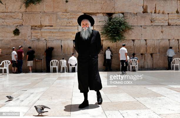A Jewish man walks by as others pray at the men's section of the Western Wall the most holy site where Jews can pray in Jerusalem's Old City on June...