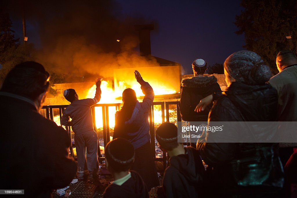 Jewish men and women throw votive candles into a burning pyre at the grave of Rabbi Yisrael Abuhatzera, known as the sage Baba Sali, on January 15, 2013 in the southern Israeli town of Netivot, Israel. Thousands of Jews, mainly of Moroccan origin, gathered to pray and hold festivities at the tomb of the respected rabbi who was known as a miracle maker by religious Jews.