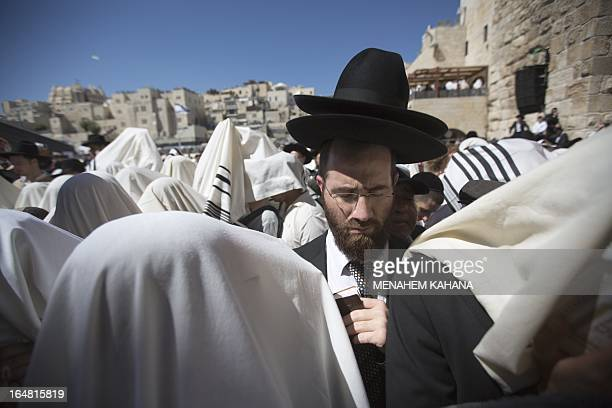 Jewish men draped in prayer shawls perform the Cohanim prayer during the Pesach holiday at the Western Wall in the Old City of Jerusalem on March 28...