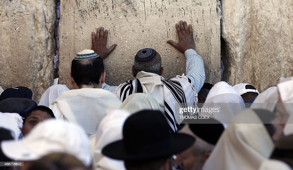 Jewish men draped in prayer shawls perform the Cohanim prayer during the Pesach holiday at the Western Wall in the Old City of Jerusalem on April 6...