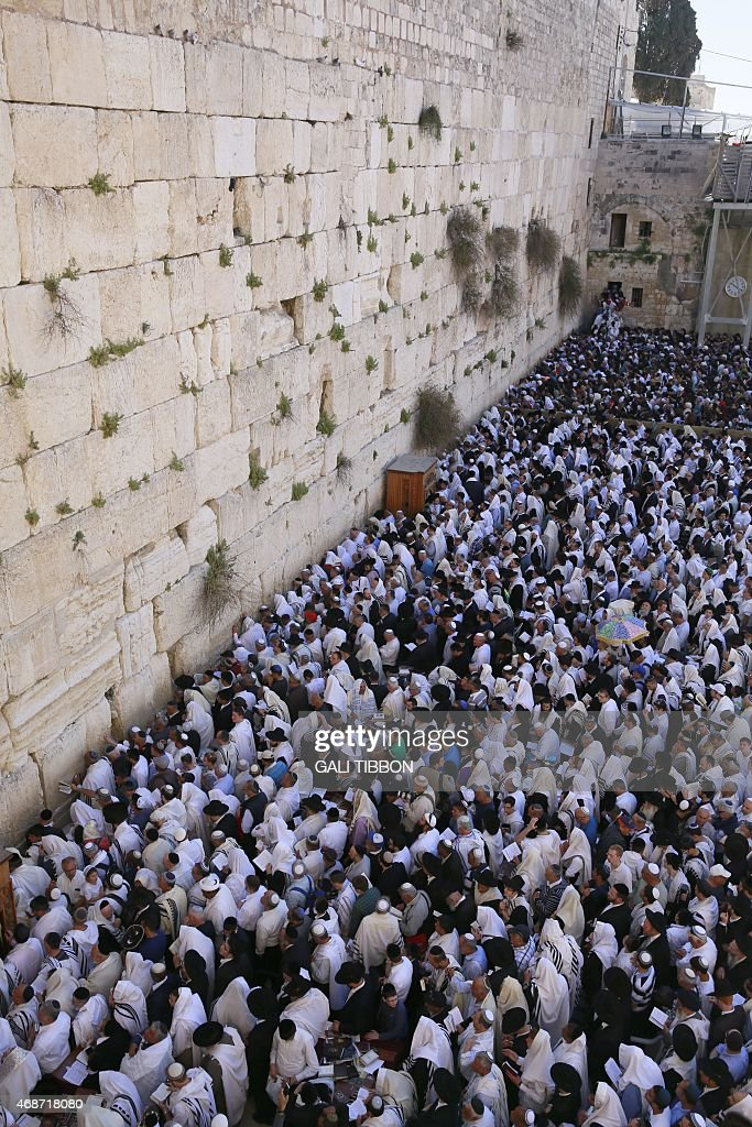 Jewish men draped in the Talith traditional prayer male shawl perform the Priestly Blessing during the Pesach holiday at the Western Wall in...