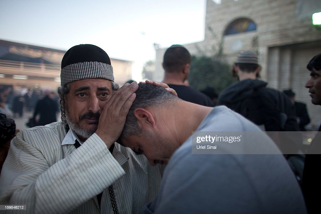 Jewish men pray at the grave of Rabbi Yisrael Abuhatzera, known as the sage Baba Sali, on January 15, 2013 in the southern Israeli town of Netivot, Israel. Thousands of Jews, mainly of Moroccan origin, gathered to pray and hold festivities at the tomb of the respected rabbi who was known as a miracle maker by religious Jews.