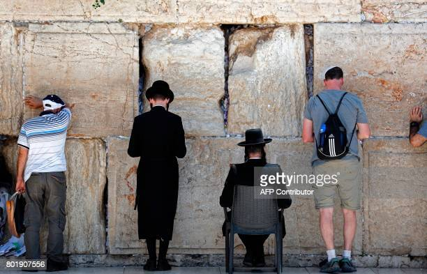 Jewish men pray at the men's section of the Western Wall the most holy site where Jews can pray in Jerusalem's Old City on June 27 2017 Israel's...
