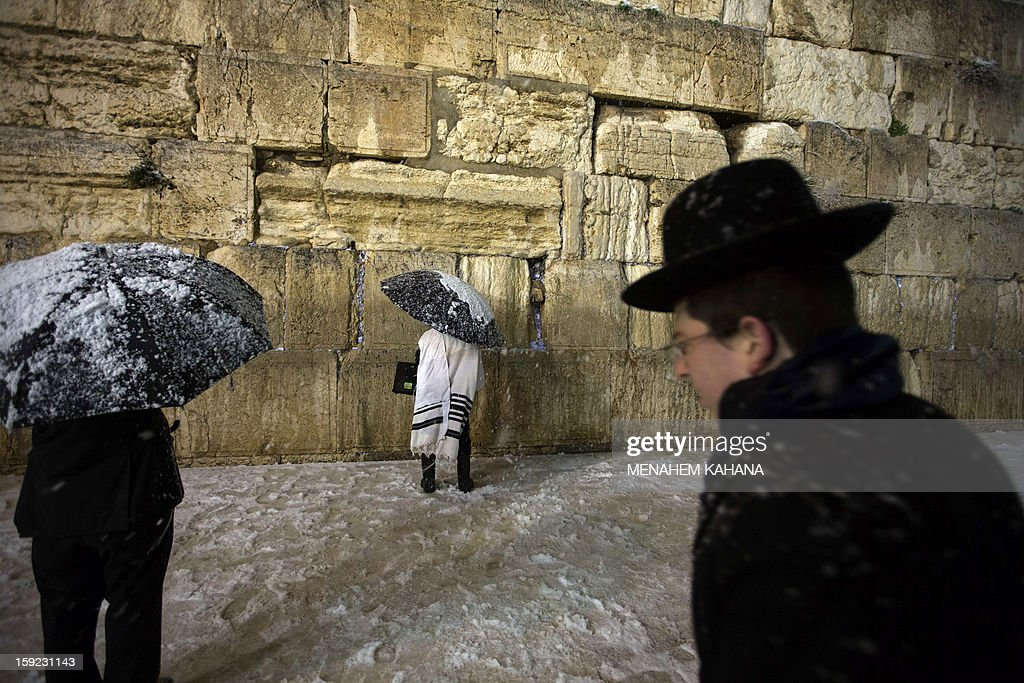 Jewish men pray at the Western Wall as snow falls in the old city of Jerusalem on January 10, 2013. Jerusalem was transformed into a winter wonderland after heavy overnight snowfall turned the Holy City and much of the region white, bringing hordes of excited children onto the streets.