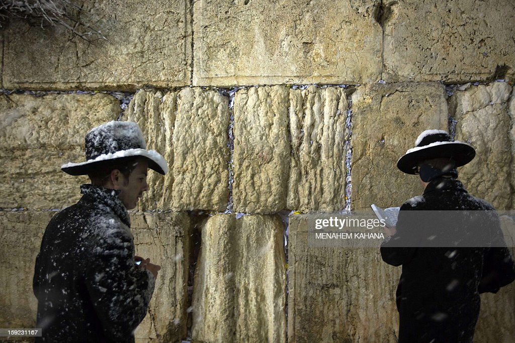 Jewish men pray at the Western Wall as snow falls in the old city of Jerusalem on January 10, 2013. Jerusalem was transformed into a winter wonderland after heavy overnight snowfall turned the Holy City and much of the region white, bringing hordes of excited children onto the streets. AFP PHOTO/MENAHEM KAHANA