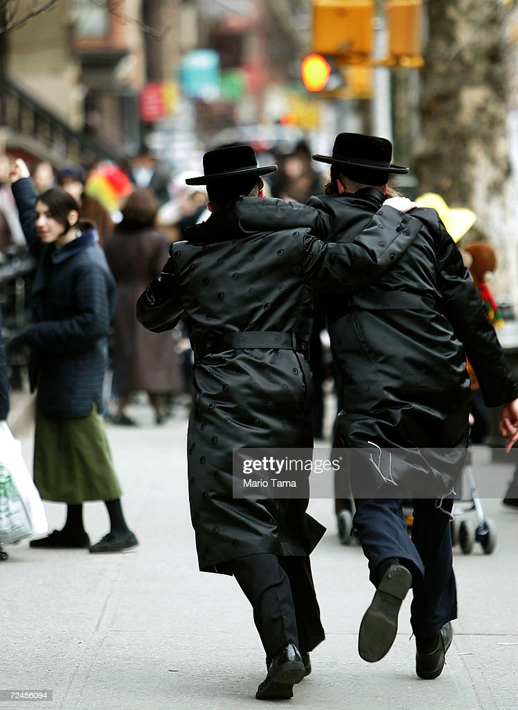 Jewish men run arm in arm down the street during Purim festivities in the Williamsburg section of Brooklyn March 25 2005 in New York City Festivities...