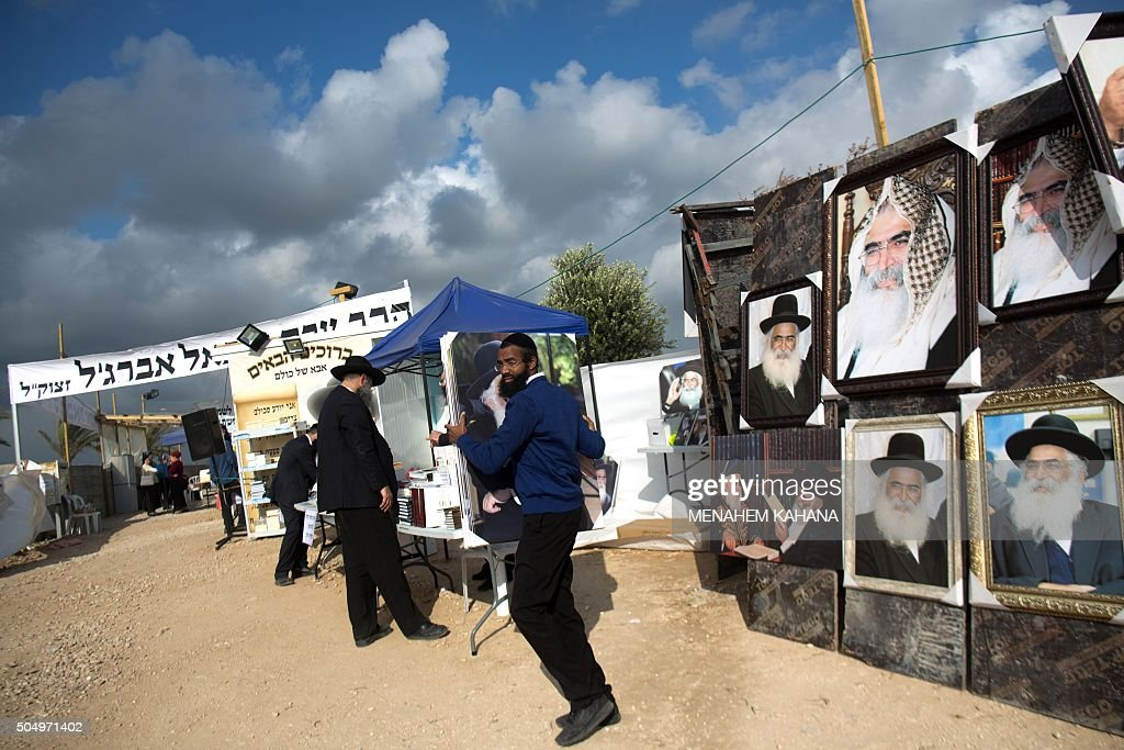 Jewish men walk past posters bearing portraits of rabbis at the tomb of Rabbi Israel Abuhaeira known as the Baba Sali during the annual pilgrimage to...
