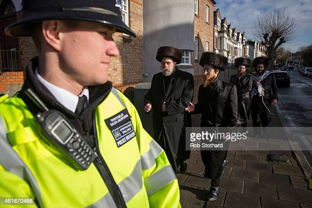 Jewish men walk towards police officers in the Stamford Hill area on January 17 2015 in London England Police have announced they will increase...