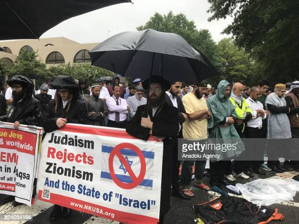 Jewish people hold banners as they stand in solidarity with Muslims while they pray behind them to protest restrictions implemented around the AlAqsa...