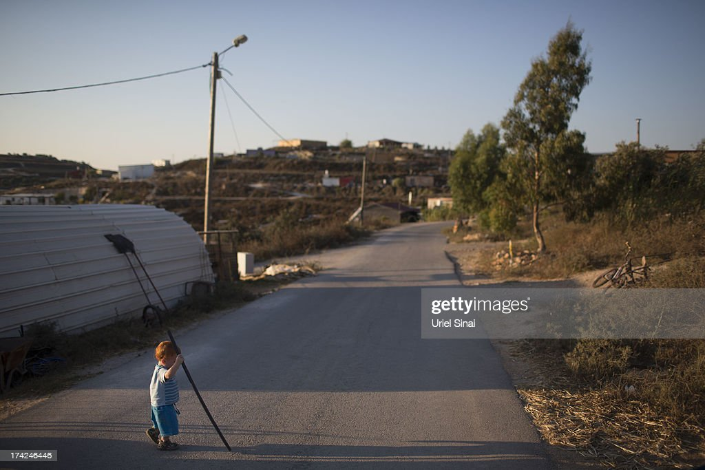 A Jewish settler boy plays outside his home on July 22, 2013 at the Jewish Settlement outpost of Havat Gilad in the West Bank. U.S. Secretary of State John Kerry announcedin a press conference in Amman last week that direct Israeli-Palestinian peace negotiations were to begin this week in Washington.
