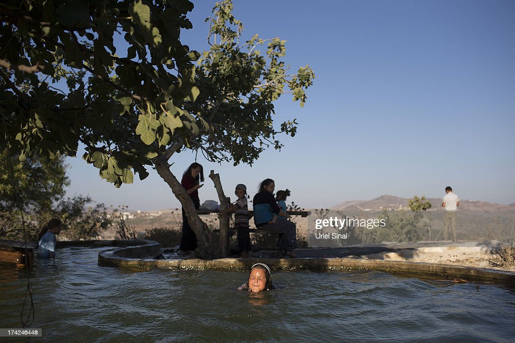 A Jewish settler boy swims in a pool on July 22, 2013 near the Jewish outpost Settlement of Har Bracha, West Bank. U.S. Secretary of State John Kerry announcedin a press conference in Amman last week that direct Israeli-Palestinian peace negotiations were to begin this week in Washington.