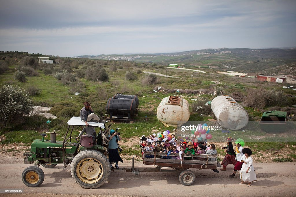 Jewish settler children wear costumes as they ride the back of a tractor ahead of the Jewish festival of Purim February 22, 2013 at the settlement outpost of Havat Gilad, West Bank. The carnival-like Purim holiday is celebrated with parades and costume parties to commemorate the deliverance of the Jewish people from a plot to exterminate them in the ancient Persian empire 2,500 years ago, as described in the Book of Esther.