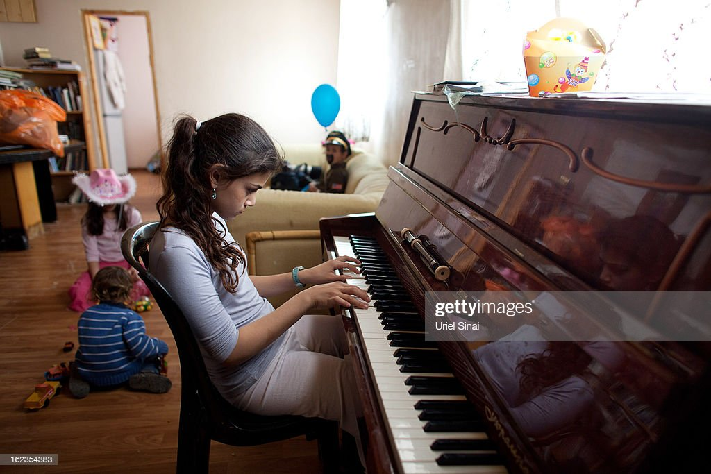 A Jewish settler girl plays the piano as her brothers and sister wear costumes ahead of the Jewish festival of Purim February 22, 2013 at the settlement outpost of Havat Gilad, West Bank. The carnival-like Purim holiday is celebrated with parades and costume parties to commemorate the deliverance of the Jewish people from a plot to exterminate them in the ancient Persian empire 2,500 years ago, as described in the Book of Esther.