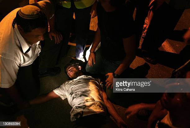 Jewish settler lies unconscious on the ground after a protest against Ariel Sharon's Disengagement plan led to violent scuffling with Israeli police...