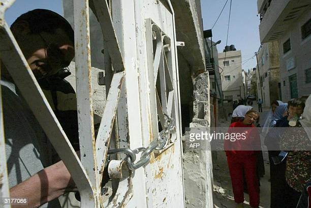 Jewish settler locks himself with chains at a building as Palestinian children look at him in the Arab neighbourhood of Silwan in Israeliannexed east...
