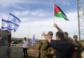 A Jewish settler places the Israeli flag on a road sign while Israeli troops encircle Palestinian villagers protesting after the Israeli army cut off...