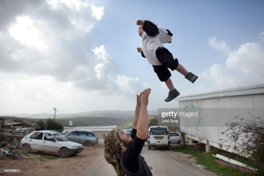A Jewish settler plays with his baby as settlers celebrate the Jewish festival of Purim February 24, 2013 at the settlement outpost of Havat Gilad, West Bank. The carnival-like Purim holiday is celebrated with parades and costume parties to commemorate the deliverance of the Jewish people from a plot to exterminate them in the ancient Persian empire 2,500 years ago, as described in the Book of Esther. (Photo by Uriel Sinai/Getty Images)Ê