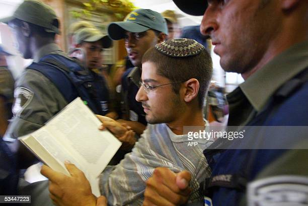 Jewish settler reads a book as is carried out of the synagogue by Israeli border police in the northern Gaza Strip settlement of Elei Sinai 21 August...