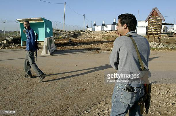 Jewish settler Sharon HarEl with his M16 assault rifle on his back chats with settlement security guard Golan Azami who is armed with an Uzi...