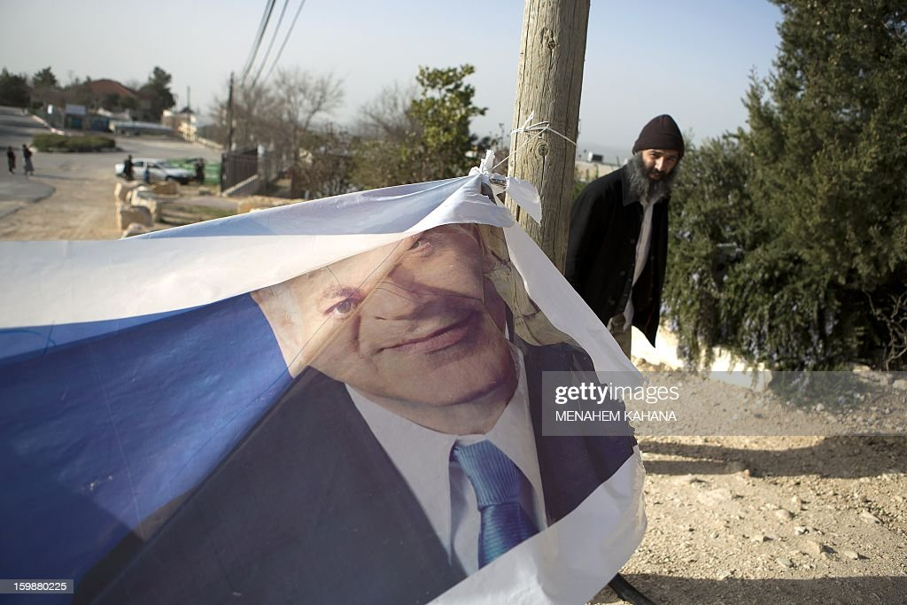 A Jewish settler walks past a campaign poster of Israeli Prime Minister Benjamin Netanyahu outside a polling station in Bat-Ayin, part of the Jewish settlement bloc of Gush Etzion, in the West Bank on January 22, 2013. Voters across Israel and in settlements peppering the occupied West Bank cast ballots for the Israeli general election at more than 10,000 polling stations, with turnout standing at 38.3 percent after seven hours of voting. AFP PHOTO/MENAHEM KAHANA