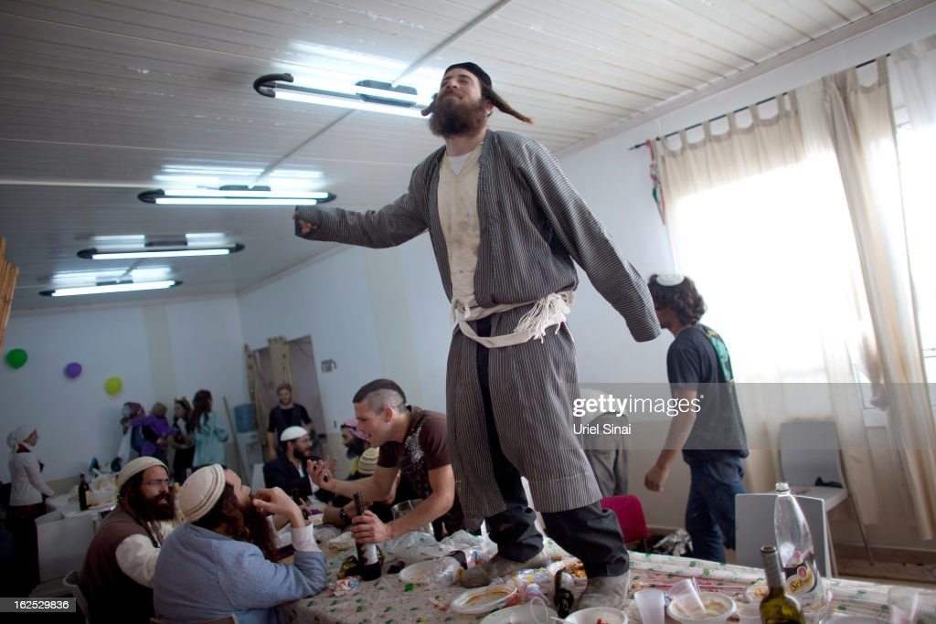 A Jewish settler wears a costume and dances on a table as they celebrate the Jewish festival of Purim February 24 2013 at the settlement outpost of...