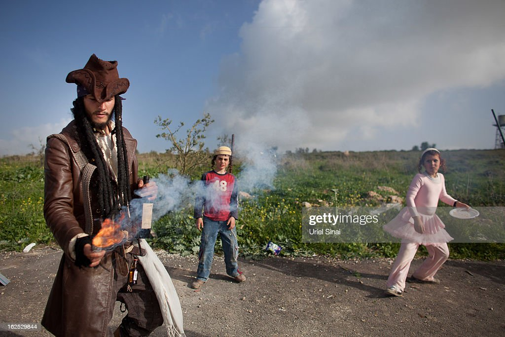 A Jewish settler wears a costume and plays with fireworks as settlers celebrate the Jewish festival of Purim February 24, 2013 at the settlement outpost of Havat Gilad, West Bank. The carnival-like Purim holiday is celebrated with parades and costume parties to commemorate the deliverance of the Jewish people from a plot to exterminate them in the ancient Persian empire 2,500 years ago, as described in the Book of Esther. (Photo by Uriel Sinai/Getty Images)Ê