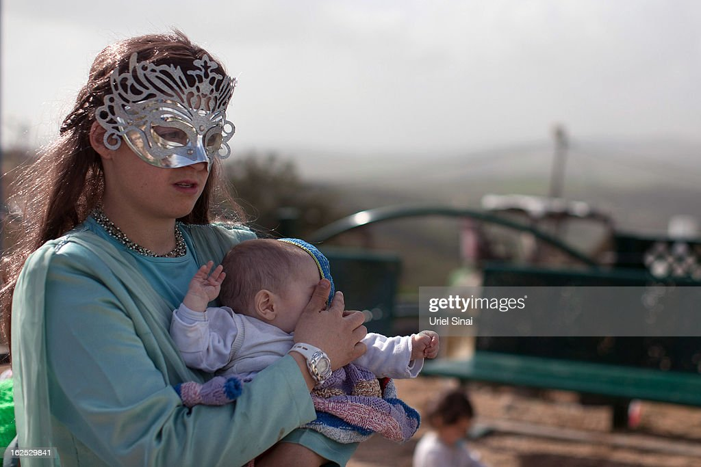 A Jewish settler wears a costume as she holds her baby as settlers celebrate the Jewish festival of Purim February 24, 2013 at the settlement outpost of Havat Gilad, West Bank. The carnival-like Purim holiday is celebrated with parades and costume parties to commemorate the deliverance of the Jewish people from a plot to exterminate them in the ancient Persian empire 2,500 years ago, as described in the Book of Esther. (Photo by Uriel Sinai/Getty Images)Ê