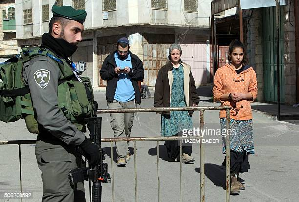 Jewish settlers are evacuated by Israeli security forces from two homes in the heart of the West Bank city of Hebron on January 22 the day after they...