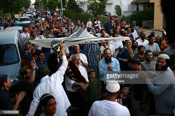Jewish settlers dance with a new Torah scroll through the streets of Neve Dekalim as it is brought to Torat HaChaim a religious institue of study in...