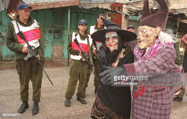 Jewish settlers disguised for the Jewish carnival day of 'Purim' pass Israeli soldiers in the West Bank town of Hebron 16 March Jews commemorate 16...