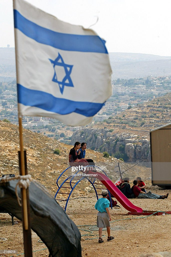 Jewish settlers gather at the Tel Haim settlers' outpost July 8, 2003 near Ramallah in the West Bank. After their appeals against eviction were turned down in Israel's supreme court, settlers at a number of illegal outposts are preparing to resist attempts by the army to implement the terms of the U.S.-backed 'road map' peace plan. The plan calls for Israel to dismantle all illegal settlements established since March 2000.