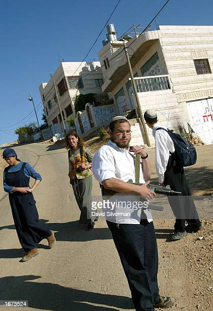 Jewish settlers one armed with an Uzi submachinegun walk down a road they call Worshippers' Way past Palestinian houses December 5 2002 in the...