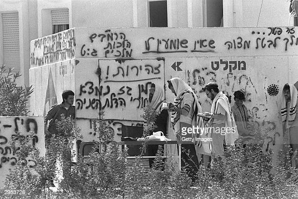 Jewish settlers pray outside a fortified bunker where they take shelter from Israeli soldiers as they resist forced evacuation April 18 1982 from...