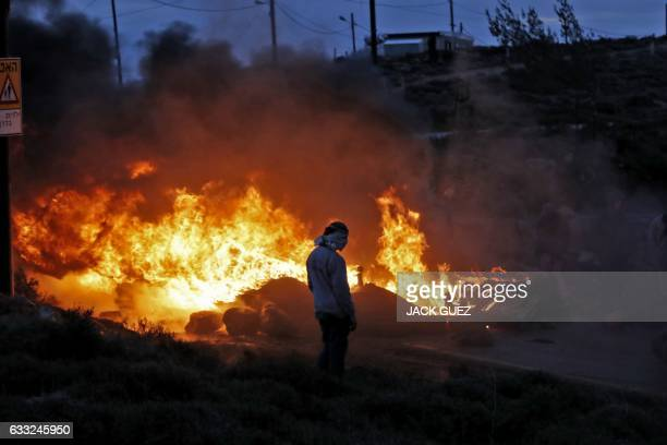 TOPSHOT CORRECTION Jewish settlers set tyres ablaze at the Amona outpost northeast of Ramallah on February 1 2017 as Israeli security forces are...