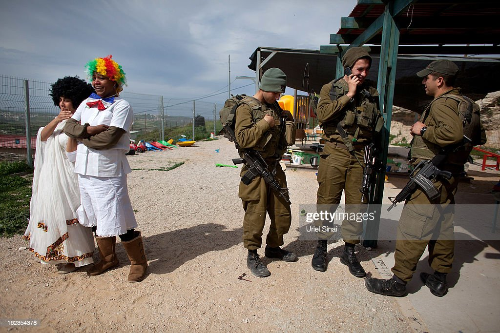 A Jewish settlers wear costumes ahead of the Jewish festival of Purim as Israeli soldiers arrive to secure a Purim parade February 22, 2013 at the settlement outpost of Havat Gilad, West Bank. The carnival-like Purim holiday is celebrated with parades and costume parties to commemorate the deliverance of the Jewish people from a plot to exterminate them in the ancient Persian empire 2,500 years ago, as described in the Book of Esther.
