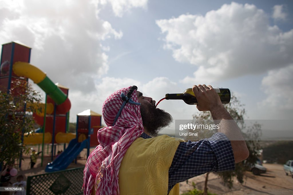 A Jewish settlers wears a costume as he drinks wine as settlers celebrate the Jewish festival of Purim February 24, 2013 at the settlement outpost of Havat Gilad, West Bank. The carnival-like Purim holiday is celebrated with parades and costume parties to commemorate the deliverance of the Jewish people from a plot to exterminate them in the ancient Persian empire 2,500 years ago, as described in the Book of Esther. (Photo by Uriel Sinai/Getty Images)Ê