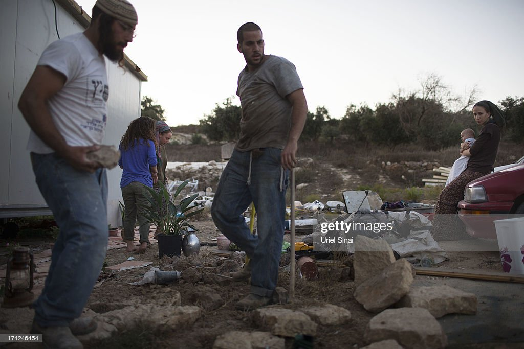 Jewish Settlers work outside their home on July 22, 2013 at the Jewish Settlement outpost of Havat Gilad in the West Bank. U.S. Secretary of State John Kerry announcedin a press conference in Amman last week that direct Israeli-Palestinian peace negotiations were to begin this week in Washington.