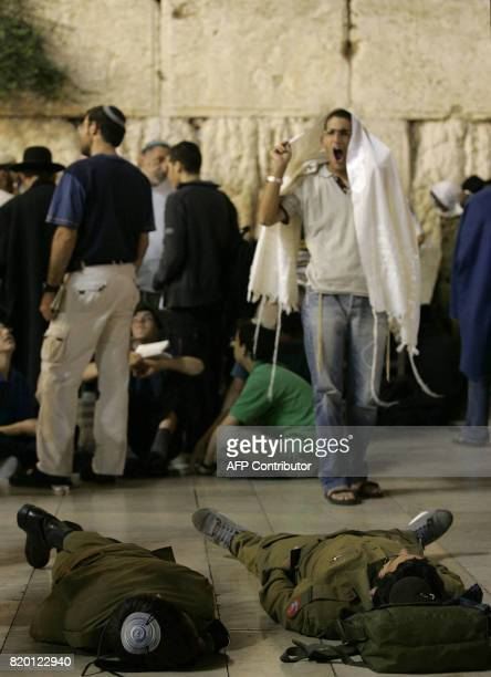 Jewish soldiers sleep while others pray during the Tisha 'Av commemoration at the Western Wall in the old city of Jerusalem early 03 August 2006...