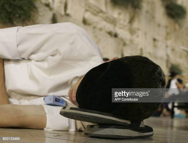 A Jewish uses his slippers as a pillow as he sleeps while others pray during the Tisha 'Av commemoration at the Western Wall in the old city of...