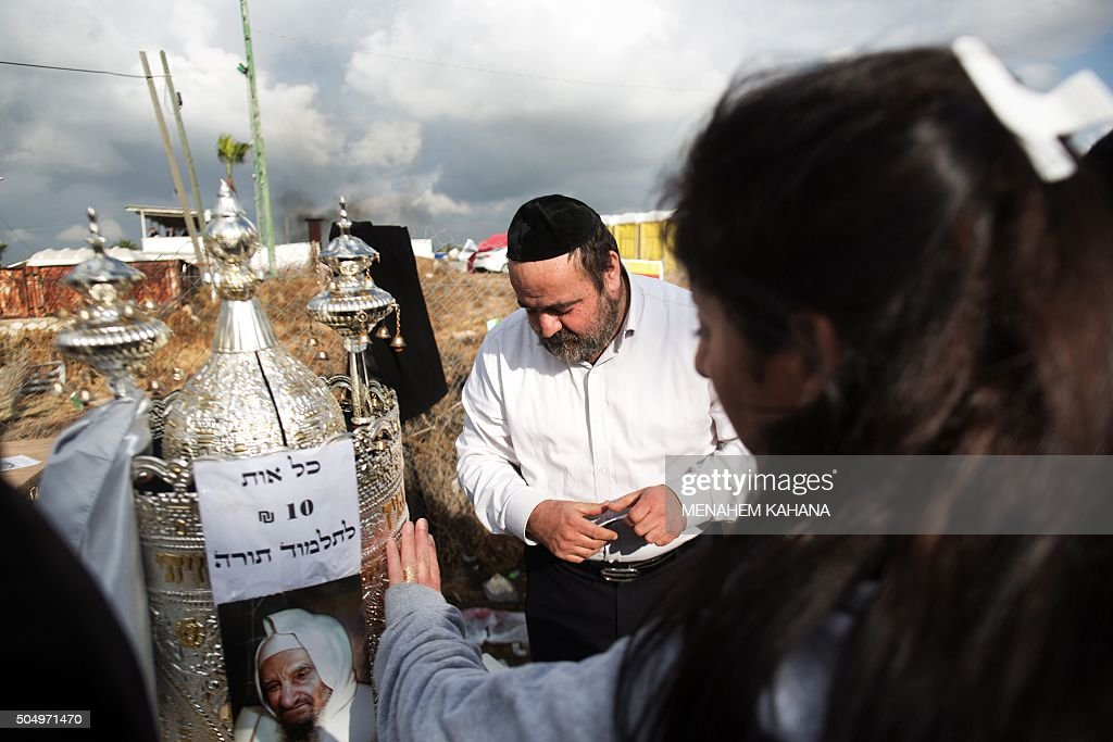 A Jewish woman places her hand over a Torah scroll at the tomb of Rabbi Israel Abuhaeira known as the Baba Sali during the annual pilgrimage to his...