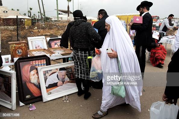 A Jewish woman walks past a stall selling portraits of rabbis at the tomb Rabbi Israel Abuhaeira known as the Baba Sali during the annual pilgrimage...