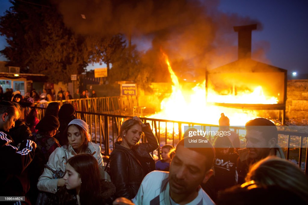 Jewish women and men pray alongside a burning pyre of votive candles at the grave of Rabbi Yisrael Abuhatzera, known as the sage Baba Sali, on January 15, 2013 in the southern Israeli town of Netivot, Israel. Thousands of Jews, mainly of Moroccan origin, gathered to pray and hold festivities at the tomb of the respected rabbi who was known as a miracle maker by religious Jews.