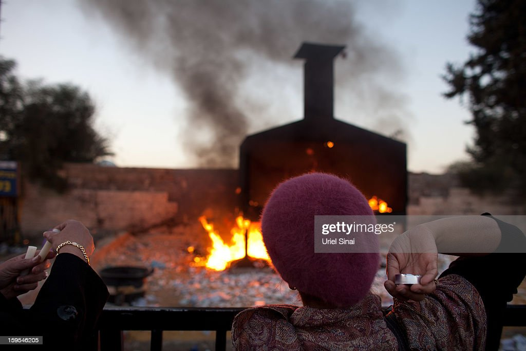 A Jewish women throws votive candles into a burning pyre at the grave of Rabbi Yisrael Abuhatzera, known as the sage Baba Sali, on January 15, 2013 in the southern Israeli town of Netivot, Israel. Thousands of Jews, mainly of Moroccan origin, gathered to pray and hold festivities at the tomb of the respected rabbi who was known as a miracle maker by religious Jews.