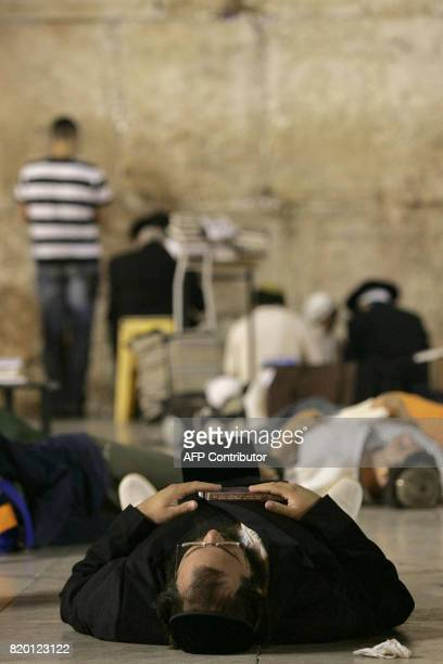 Jews sleep while others pray during the Tisha 'Av commemoration at the Western Wall in the old city of Jerusalem early 03 August 2006 Tisha 'Av...